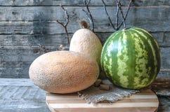 Deux melon et pastèque mûrs sur la planche à découper rayée Photos stock