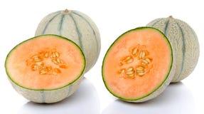Deux melons entiers et deux moitiés Photographie stock