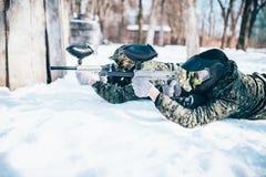 Deux mensonges de joueurs de paintball sur la neige photographie stock libre de droits