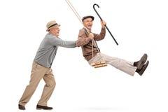 Deux messieurs supérieurs balançant sur une oscillation Photographie stock