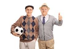 Deux messieurs supérieurs tenant un football Photographie stock