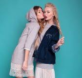 Deux modèles dans les robes et des vestes posant sur le fond bleu photo libre de droits