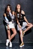 Deux modèles de sourire de brune dans le hippie occasionnel d'été vêtx sur le blanc Image stock