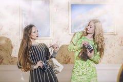 Deux modèles femelles dans des robes à la mode avec des appareils-photo de vintage Images libres de droits