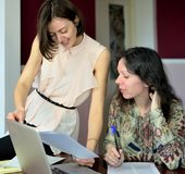 Deux mod?les en passant habill?s de jeunes dames se reposent sur un bureau dans un bureau de cru et discutent les documents mod?l photo libre de droits