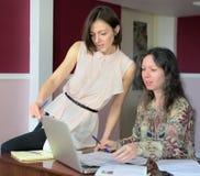 Deux mod?les en passant habill?s de jeunes dames se reposent sur un bureau dans un bureau de cru et discutent les documents mod?l photographie stock libre de droits