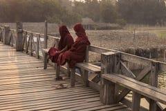 Deux moines birmans asseyant sur le pont d'U Bein image libre de droits