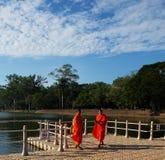 Deux moines bouddhistes dans des robes longues oranges se tiennent sur le pont Jeunes ministres de religieux image stock