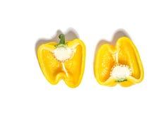 Deux moitiés de jaune ont coupé en tranches le poivre d'isolement sur le blanc Image libre de droits
