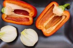 Deux moitiés de poivron doux rouge et deux moitiés d'oignon d'un plat noir Photo stock