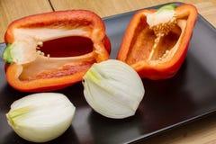 Deux moitiés de poivron doux rouge et deux moitiés d'oignon d'un plat noir Image stock