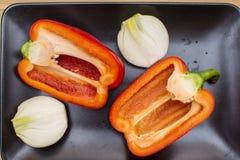 Deux moitiés de poivron doux rouge et deux moitiés d'oignon d'un plat noir Photographie stock