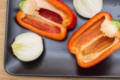 Deux moitiés de poivron doux rouge et deux moitiés d'oignon d'un plat noir Image libre de droits