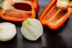 Deux moitiés de poivron doux rouge et deux moitiés d'oignon d'un plat noir Images libres de droits