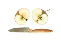 Deux moitiés de pomme et d'un couteau Images stock