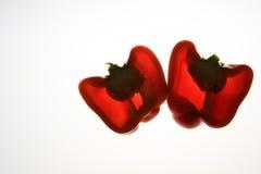 Deux moitiés des poivrons rouges, éclairées à contre-jour sur le blanc d'isolement Photo libre de droits