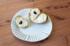 Deux morceaux d'annona cherimola mûr de fruit de chérimolier d'un plat fait main cannelé, fond en bois de table photo libre de droits