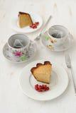 Deux morceaux de gâteau avec deux tasses de thé Photographie stock