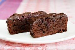 Deux morceaux de gâteau de chocolat foncé avec des cerises dans le plat blanc Images stock