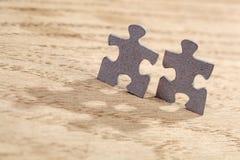 Deux morceaux de puzzle denteux sur la table Photos stock
