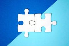Deux morceaux de puzzle se relient sur le papier bleu de couleur de la géométrie Photos stock