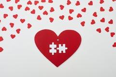 Deux morceaux de puzzle sur la carte rouge de carton Photos stock