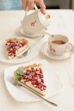 Deux morceaux de tarte de baie avec le remplissage fouetté de crème et d'une tasse de thé Photo stock