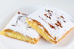 Deux morceaux de tarte de fromage d'un plat, fond blanc Photos libres de droits