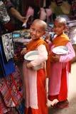 Deux nonnes d'enfant avec des cuvettes d'aumône ont rempli du riz, Birmanie image libre de droits