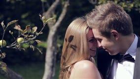 Deux nouveaux mariés embrassant à la pomme dans le jardin banque de vidéos