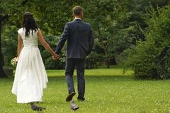 Deux nouveaux mariés marchant en parc tenant des mains photographie stock