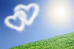 Deux nuages en forme de coeur et le soleil Photographie stock libre de droits