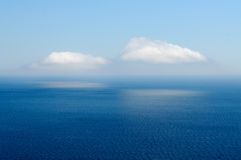 Deux nuages reflétés en mer Photo stock