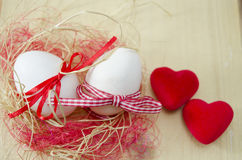 Deux oeufs blancs dans un nid et deux coeurs Image stock