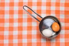 Deux oeufs dans la casserole sur la serviette checered Image libre de droits