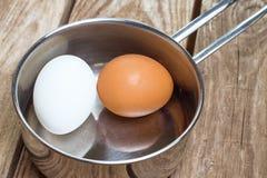 Deux oeufs dans la casserole sur la table en bois Image stock