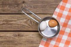 Deux oeufs dans la casserole sur la table en bois Photographie stock