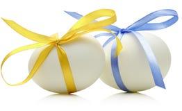 Deux oeufs de pâques avec l'arc bleu et jaune de fête sur le whi Photographie stock
