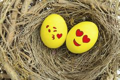 Deux oeufs de pâques peints avec des emojis dans l'amour, placé dans un nid Photos libres de droits