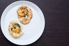 Deux oeufs de poulet frit avec des verts sur un plateau blanc sur une table en bois aussi idéale comme petit déjeuner images libres de droits