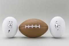 Deux oeufs regardent avec le visage étrange à un ballon de rugby Photographie stock