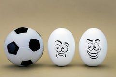Deux oeufs regardent avec le visage étrange à un ballon du football Photo stock