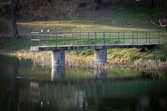 Deux oiseaux blancs se reposant sur l'extrémité d'un pont au-dessus d'un petit étang photos stock
