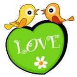 Deux oiseaux d'amour se reposant sur un coeur Photographie stock
