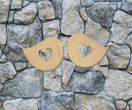 Deux oiseaux en bois avec des coeurs sur un fond en pierre image libre de droits