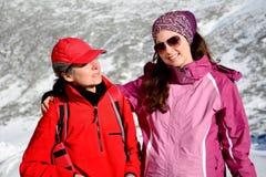 Deux ont équipé des femmes de randonneur étreignant dans une haute montagne d'hiver Mère et fille Images stock