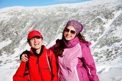 Deux ont équipé des femmes de randonneur étreignant dans une haute montagne d'hiver Mère et fille Image libre de droits