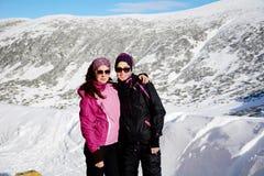 Deux ont équipé des femmes de randonneur étreignant dans une haute montagne d'hiver soeurs Images stock