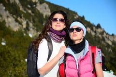 Deux ont équipé des femmes de randonneur dans une haute montagne d'hiver Images stock