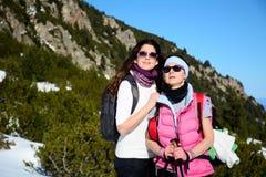 Deux ont équipé des femmes de randonneur dans une haute montagne d'hiver Image stock